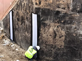 Reinforcing fabric adhered to wall with hot asphalt waterproofing