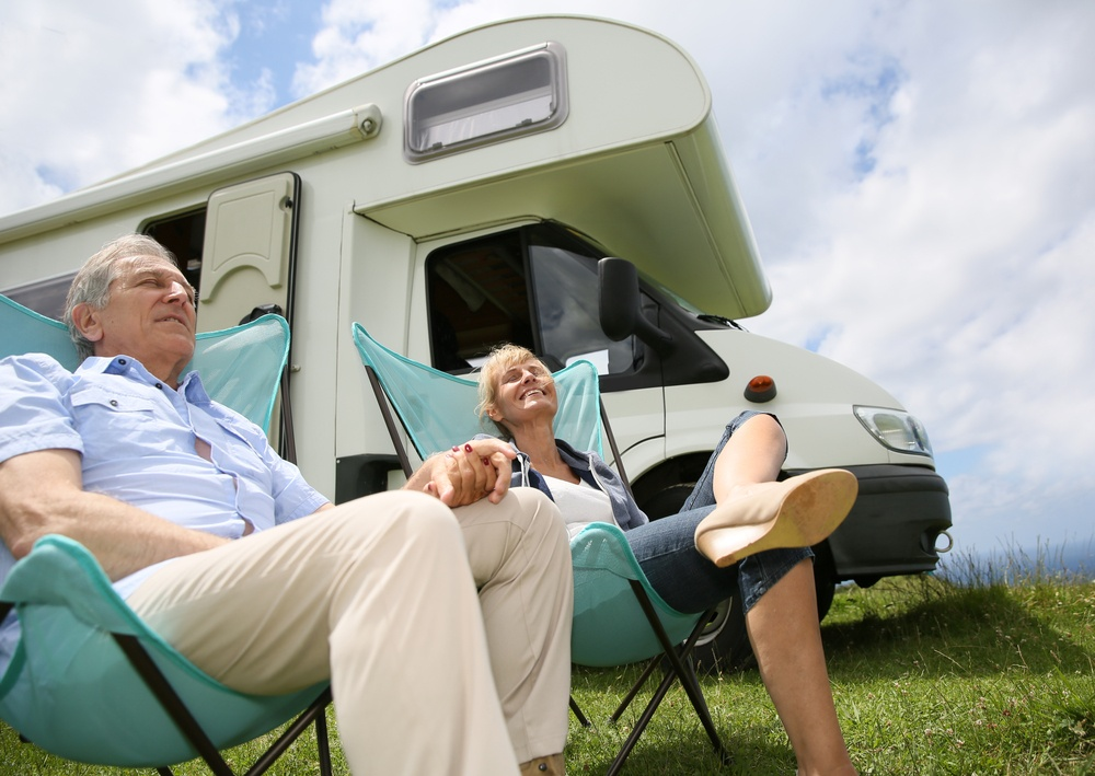Senior couple relaxing in camping folding chairs, camper in background.jpeg